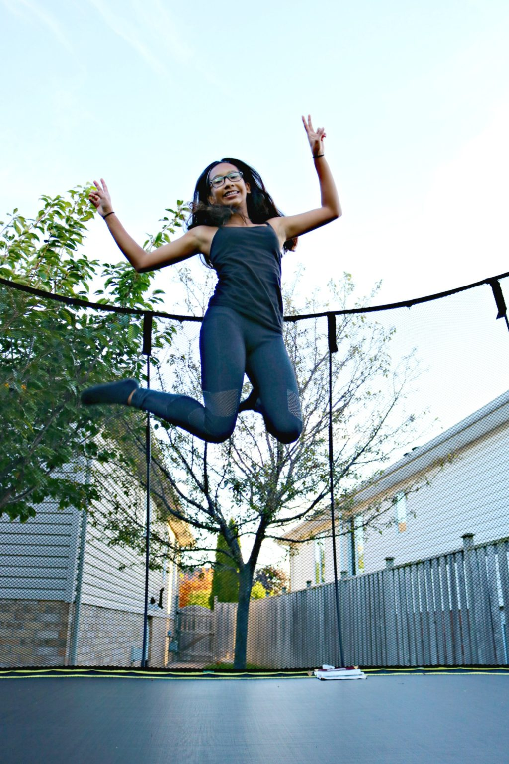 A girl jumps on a trampoline, her legs are both up and she's giving the peace sign.