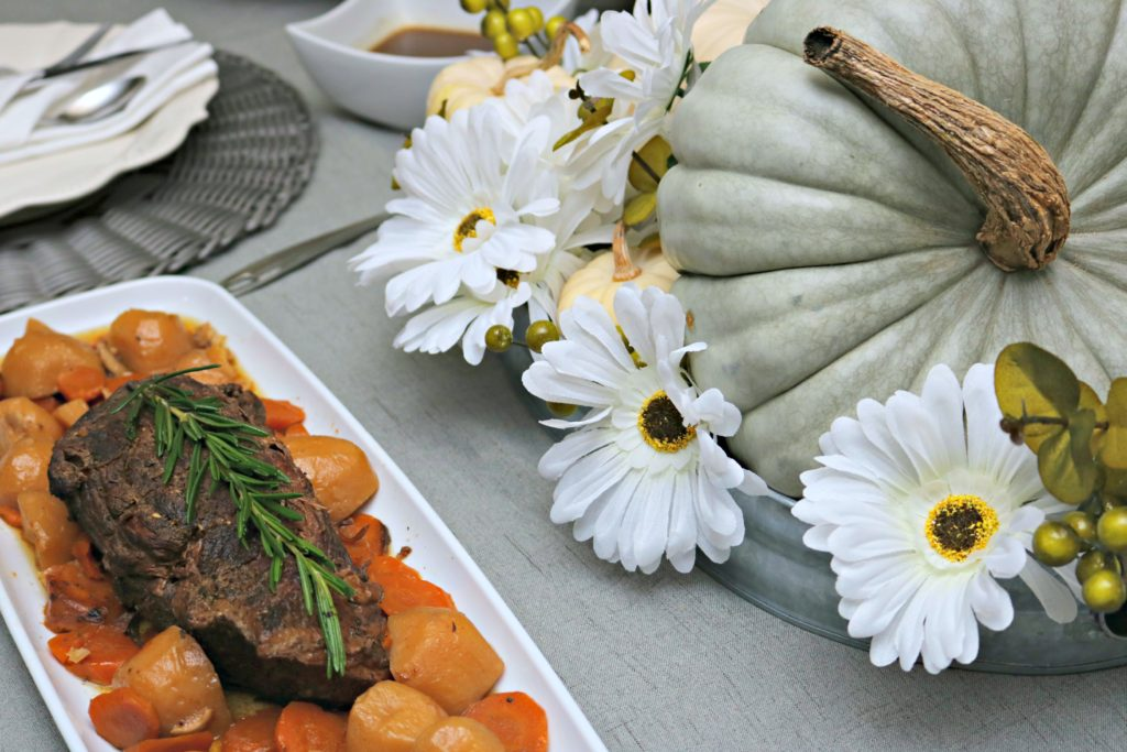 A close up of a beef roast with potatoes and carrots. A pumpkin centerpiece is shown.