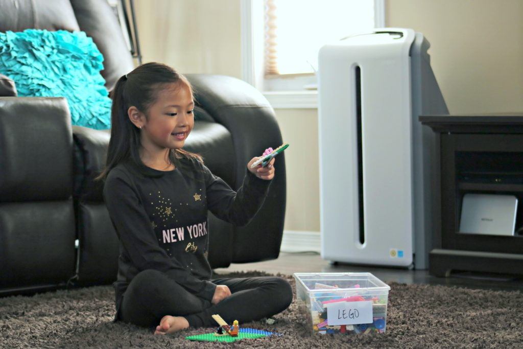 A little girl plays on her carpet in the living room with LEGOS, you can see the Atmosphere SKY Air Treatment machine behind her.