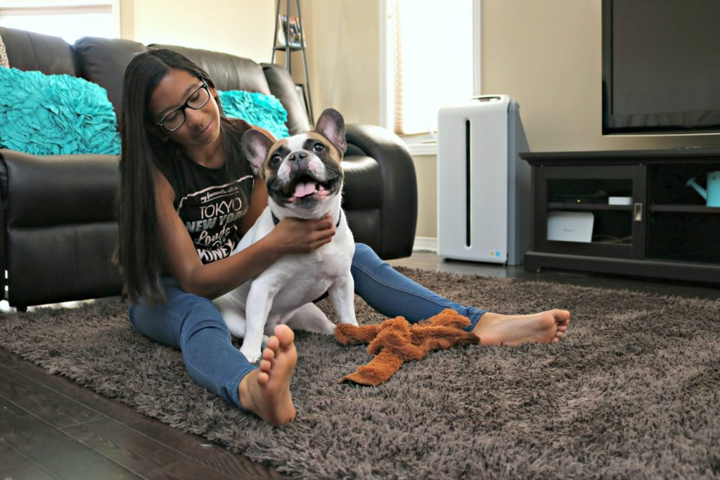 Gabby, a teen, sits and pets her dog on the carpet. The Atmosphere SKY Air Treatment System is seen in the back.