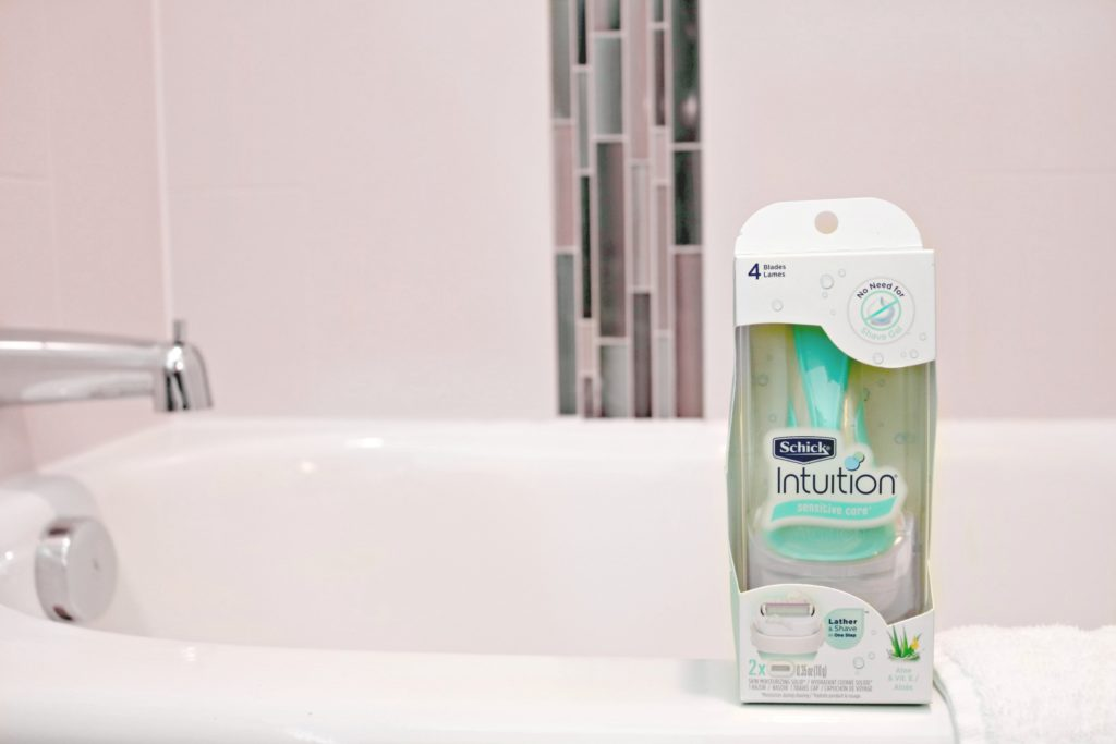 A teal Schick Intuition razor sits on a bath tub, ready to be used.