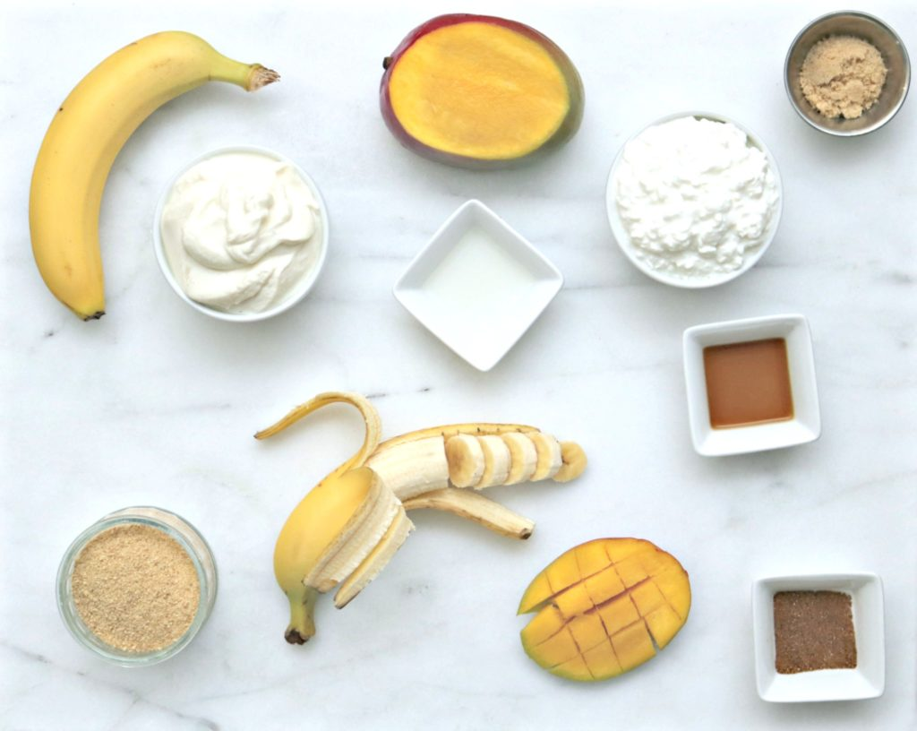 A flat lay of all the ingredients need for the recipe. Bananas, yogurt, cottage cheese, syrup, cinnamon, milk, mango, brown sugar and more.