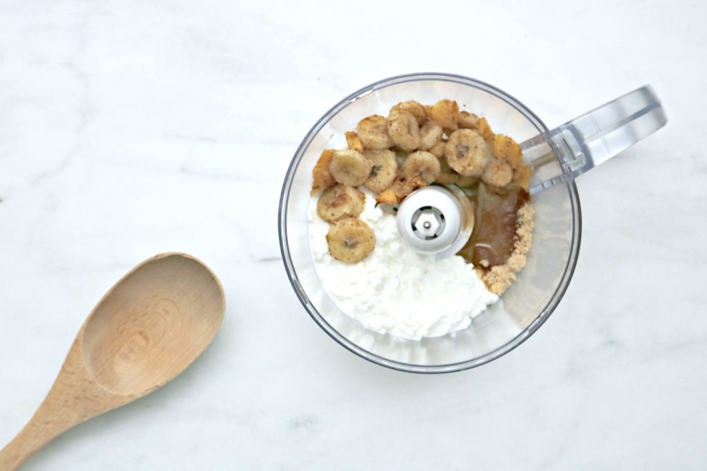 Roasted fruits, sugar, syrup, and cottage cheese being blended in a food processor.