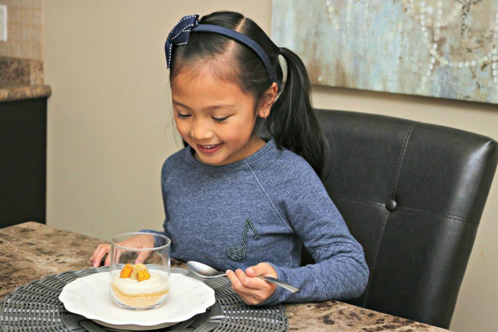 Mimi smiles while she spoons the Mango Cheesecake dessert.