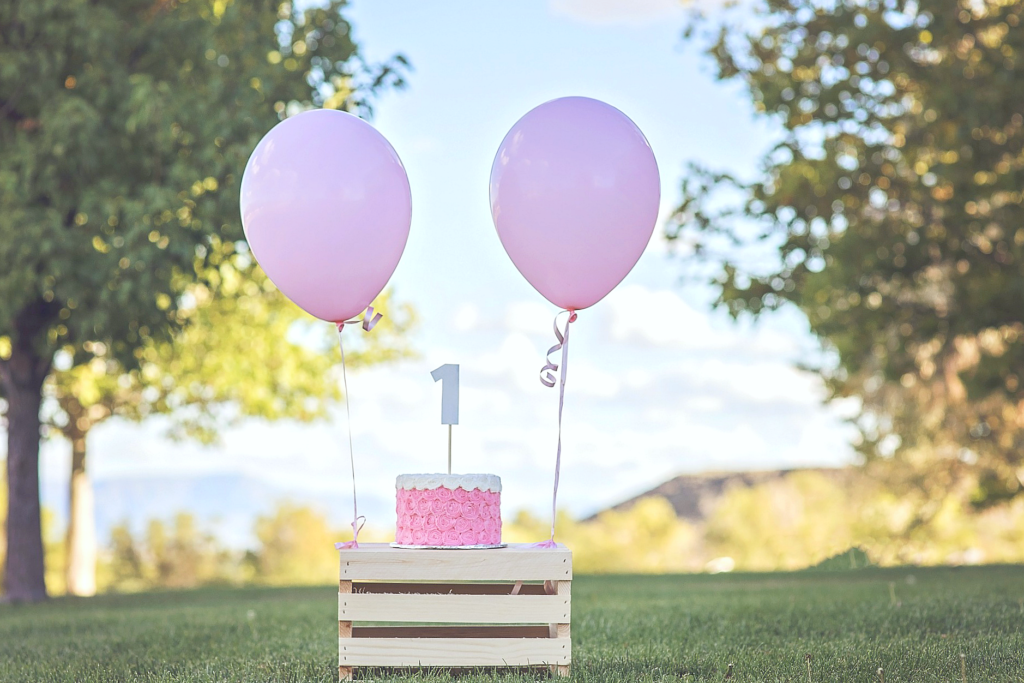 A crate holds a child's Birthday cake with two pink balloons tied to it.