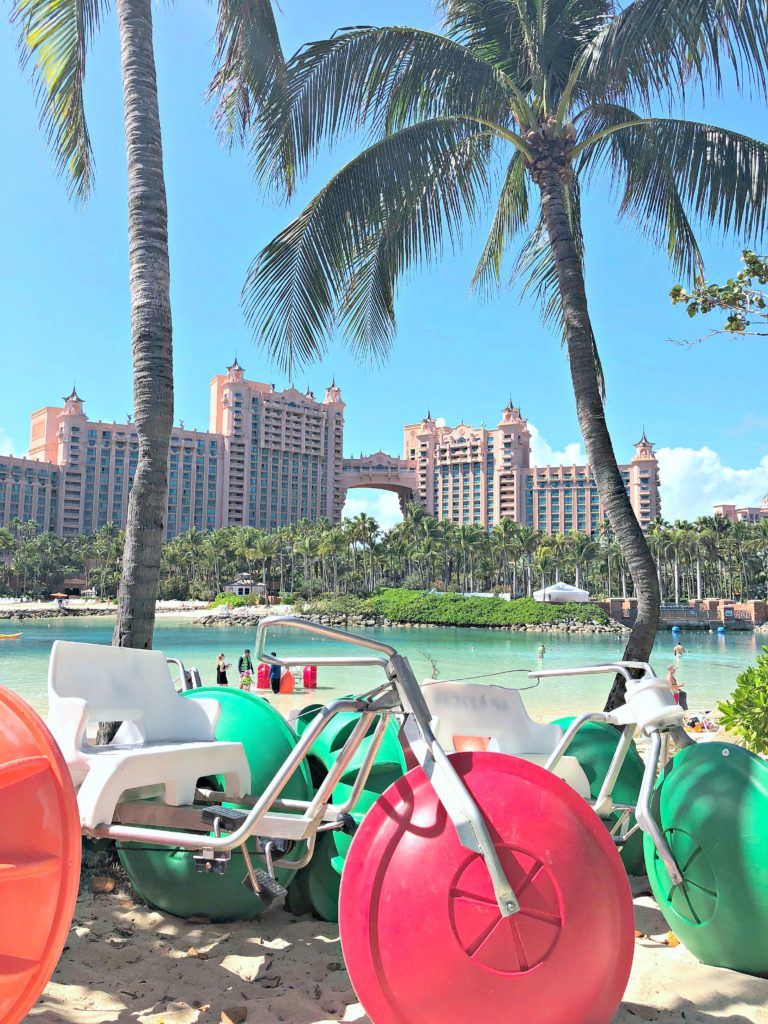 Atlantis resort is shown between palm trees while water trikes are underneath.