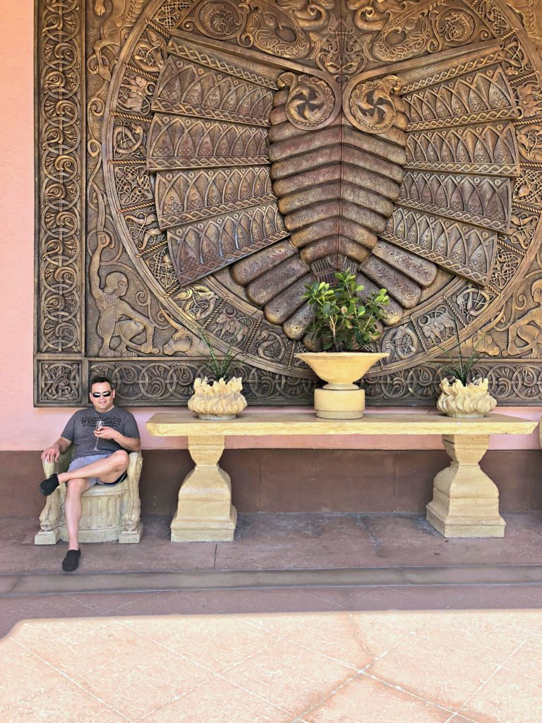 A gentleman sits in front of a huge art piece in Atlantis Resort and enjoys a glass a wine.