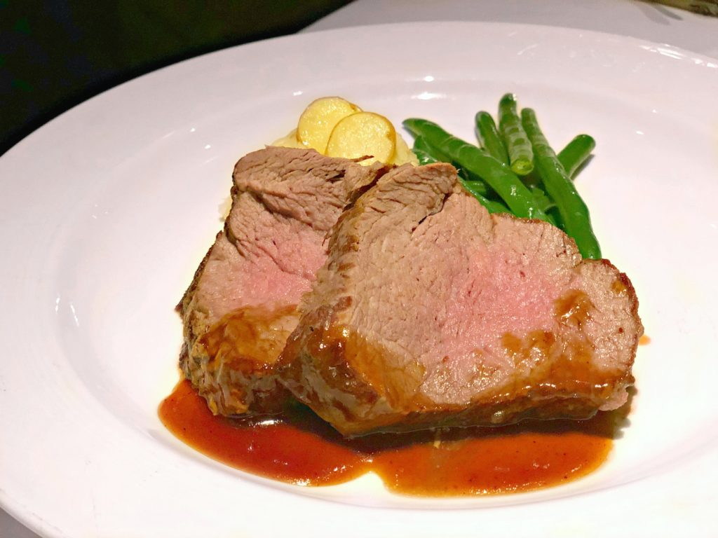 Two delicious tenderloins with green beans and mashed potatoes.