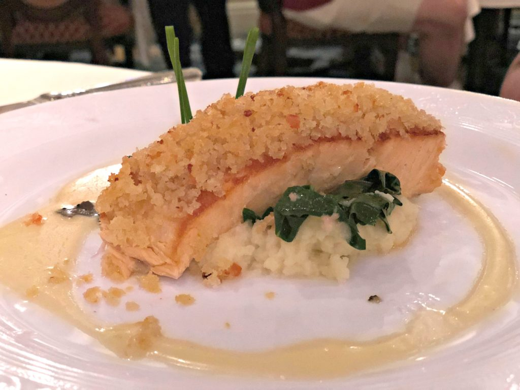A salmon steak that is bread crusted on a bed of risotto.