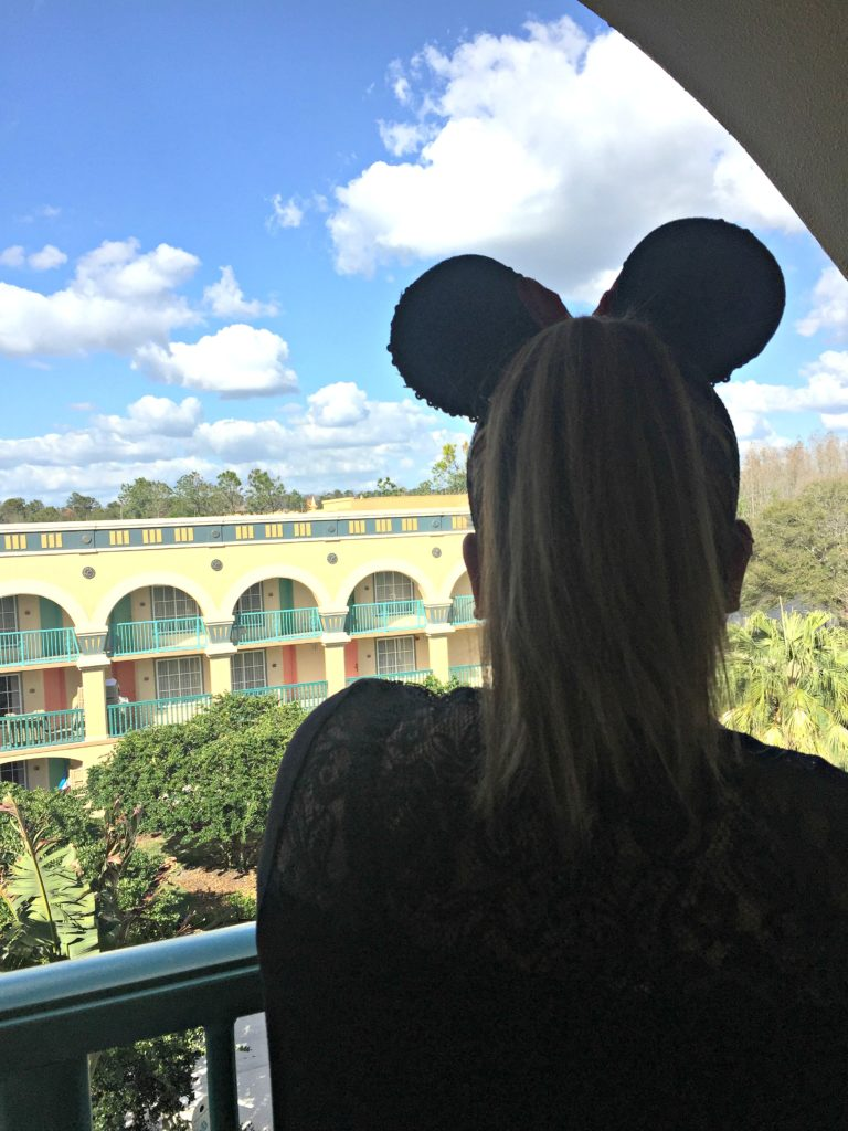 A woman looks out the Coronado Springs resort with her Minnie Ears.
