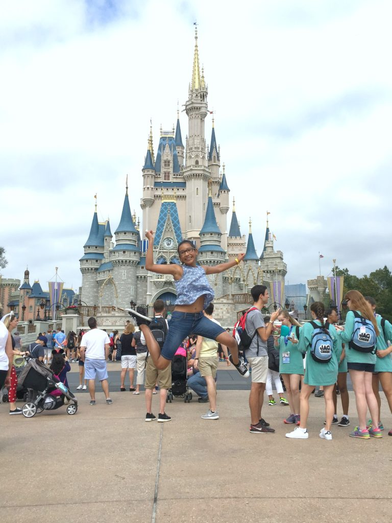 A girl jumps in front of Cinderella's castle in Magic Kingdom.