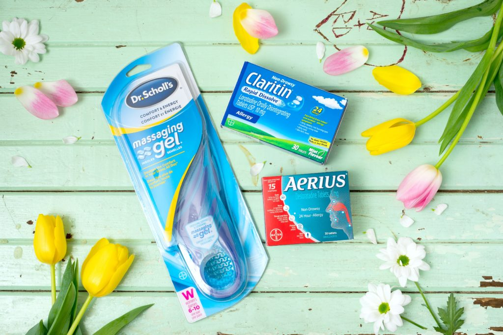A teal wooden table with Dr. Scholl's insoles, a box of Claritin and Aerius with flowers strewn about.