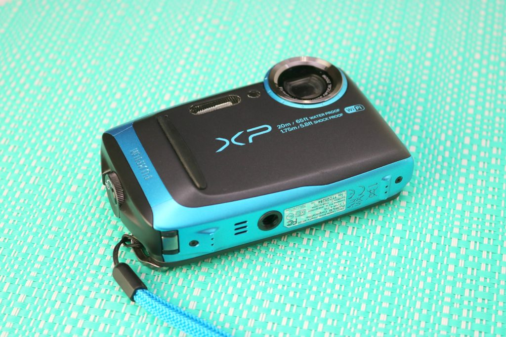 Fuji XP 120 camera lies on a teal backdrop.