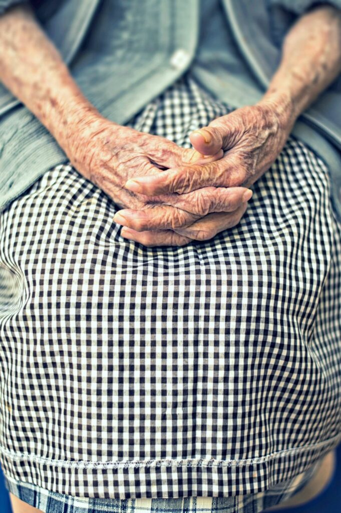 Older person sitting with fingers intertwined on lap.