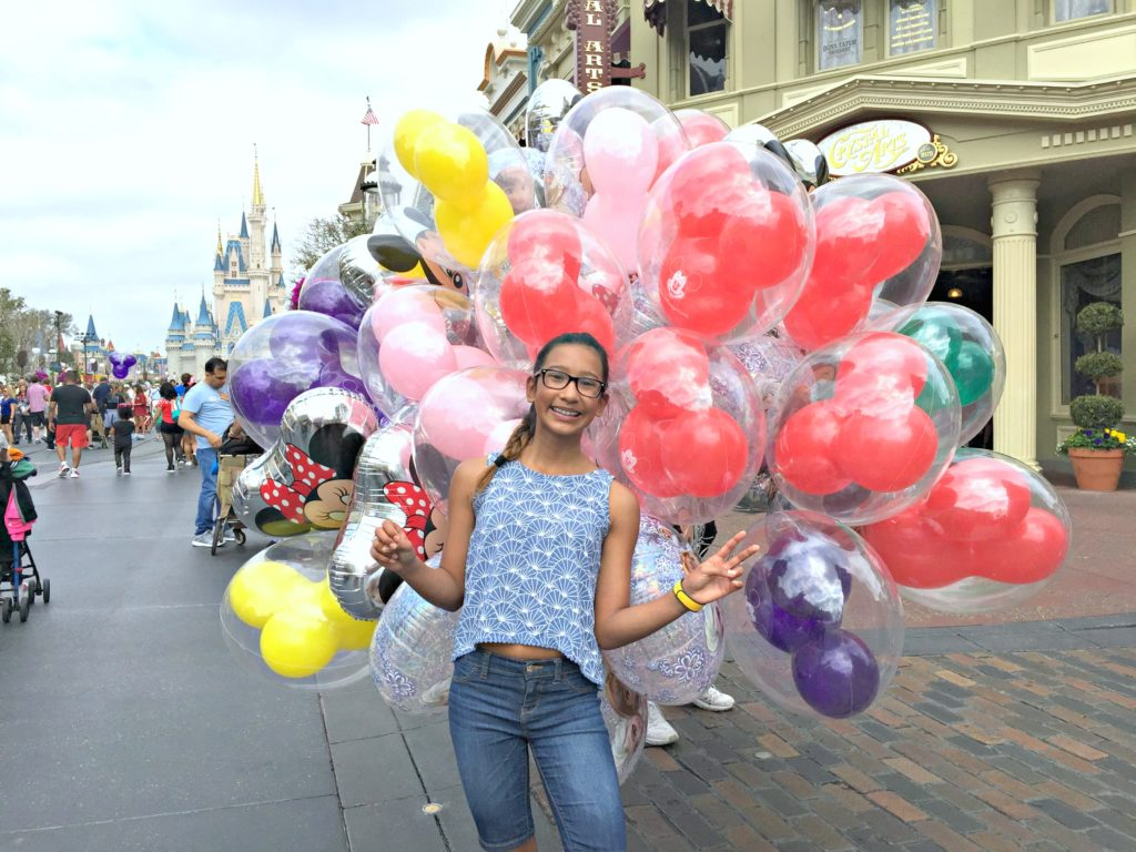 A teenager holds the famous Mickey balloons while the castle is in the background.