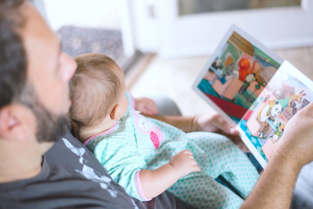 Baby sits and reads with her father on couch.