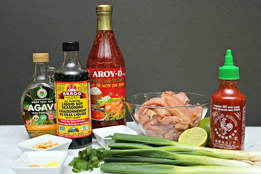 Ingredients that are needed for the recipe are shown: Thai chili sauce, soy sauce, agave, sriracha, green onions, spices, peanuts, chicken thighs and limes.