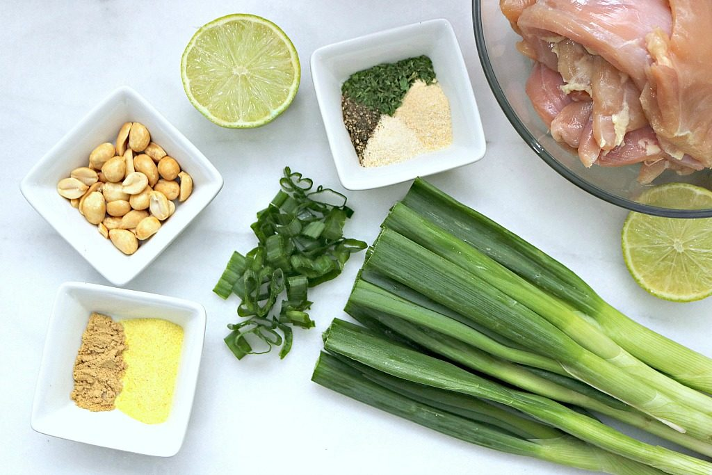 Ingredients are shown, peanuts, ginger, adobo, pepper, onion and garlic powder, lime, parsley, green onions, and chicken thighs.