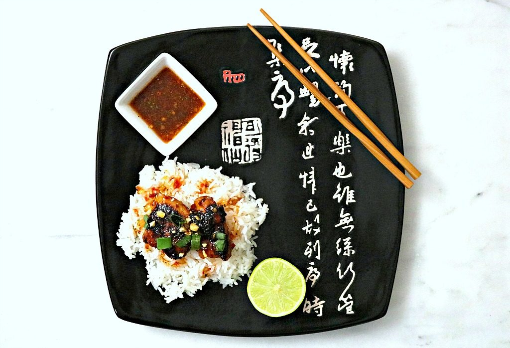 A flat plate is topped with rice, Thai-glazed chicken thighs, a side of sauce, lime, and chopsticks.