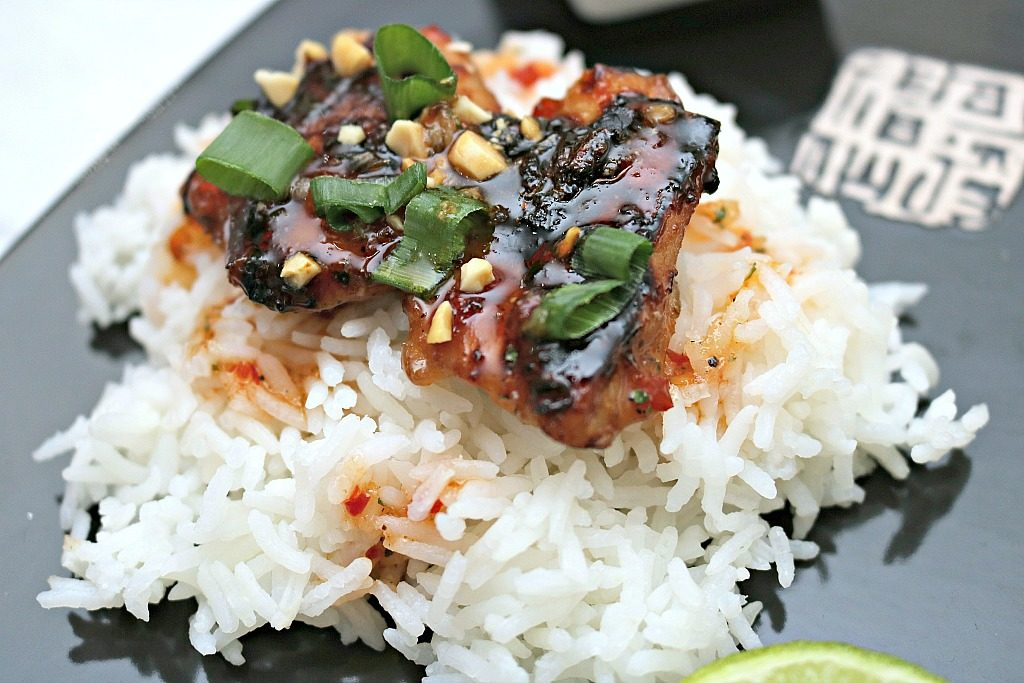 A bed of white steamed rice is topped with the Thai-glazed chicken thighs with a lime on the side.