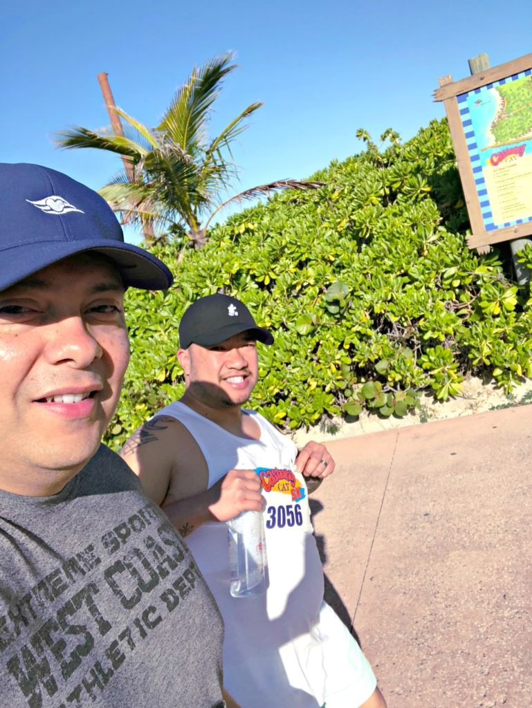 Two men take a selfie while walking the 5K at Disney's Castaway Cay.