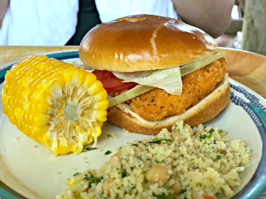 Spicy chicken sandwich at Castaway Cay with corn on the cob and tabouli.