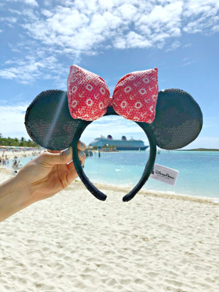 A woman holds up Disney Cruise Line Minnie ears and frames the Disney Cruise Ship, the Dream.