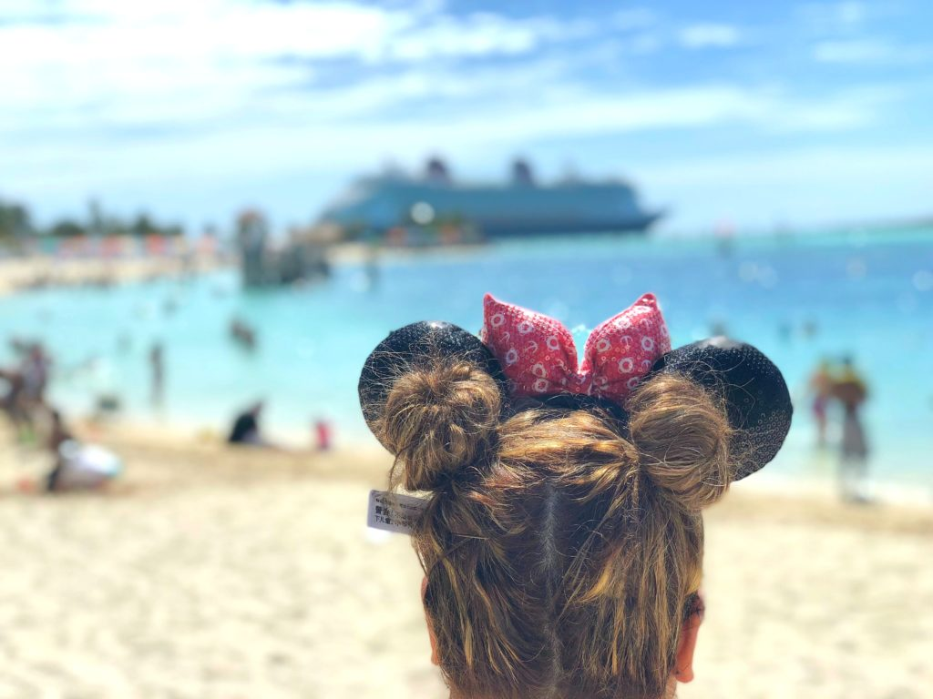 Nancy Polanco from Whispered Inspirations wears Disney Cruise Minnie ears and looks towards the Disney Dream in the Bahamas.