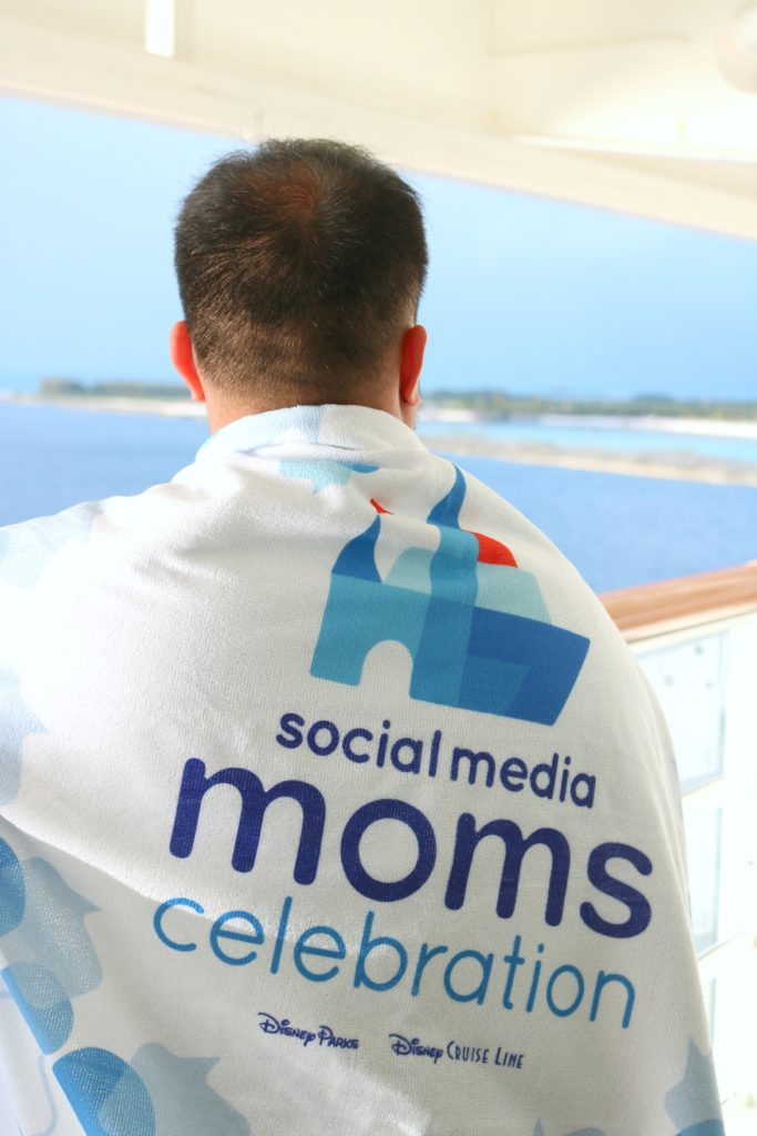 A man looks out to Castaway Cay with the Disney Social Media Moms Celebration towel on his back.