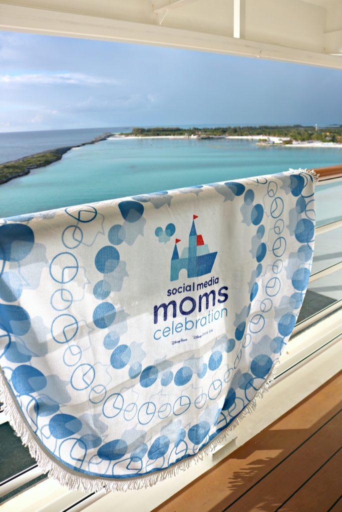 A #DisneySMMC beach towel hangs over the balcony ledge of the Disney Dream.