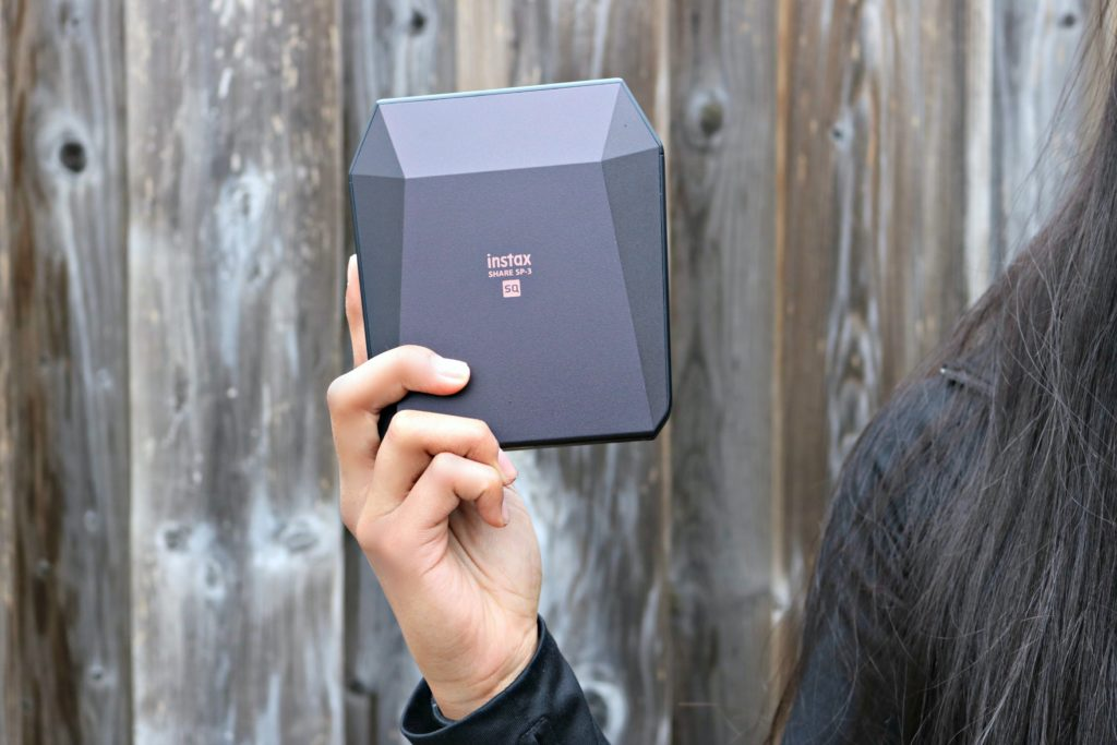 The Instax Square Share PS-1 printer shown by a teen.