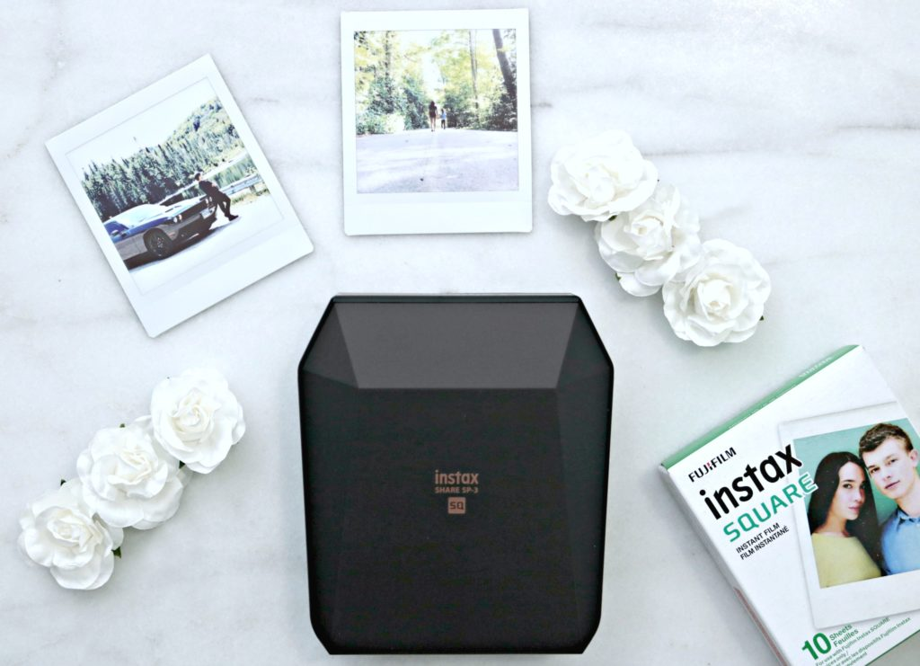 Instax printer with printed out square pictures and flowers.