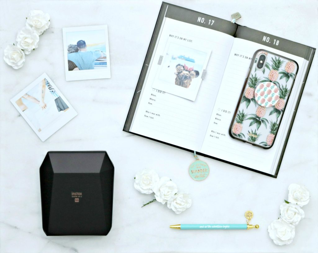 An open bucket list journal with Instax printer, printed out pictures, a pen, and a phone are shown.