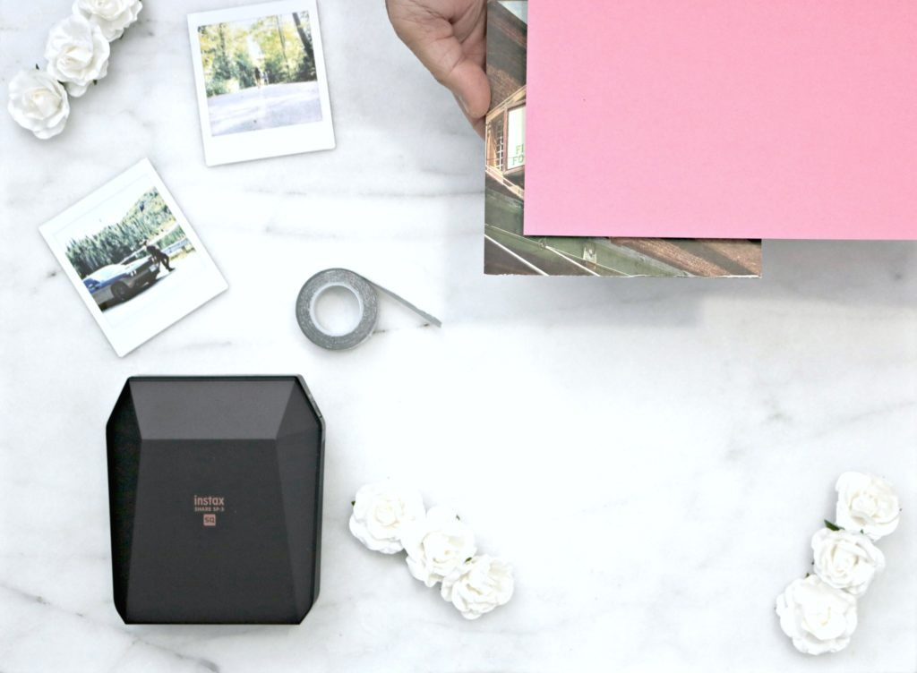 A printer with pictures, cardstock paper, flowers and tape are shown for a DIY project.