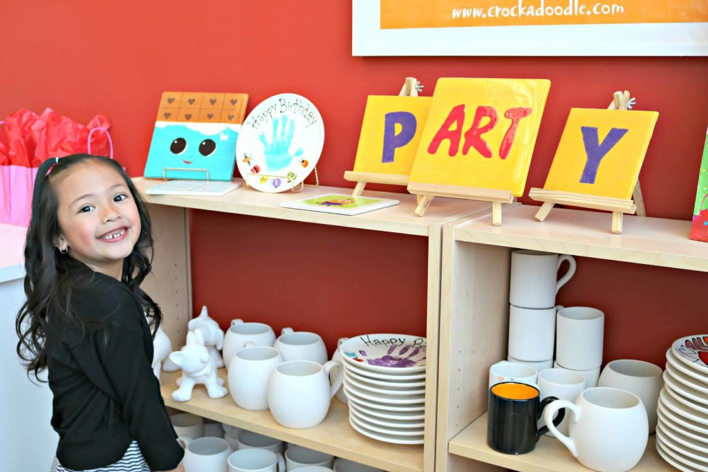 A little girl is excited to start her birthday party and stands in front of pottery.