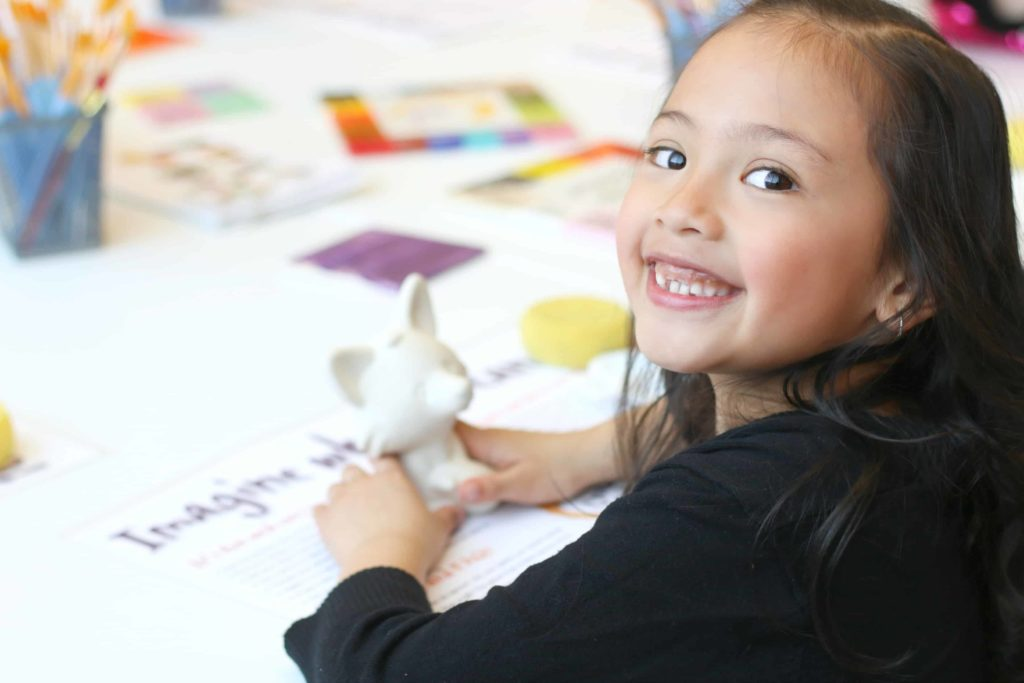 A little girl waits for paint to paint her fox pottery piece at Crock A Doodle.