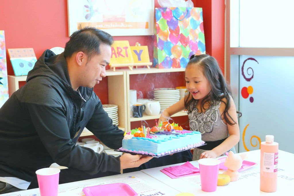 A little girl excitedly blows out her candles on her cake at Crock A Doodle.