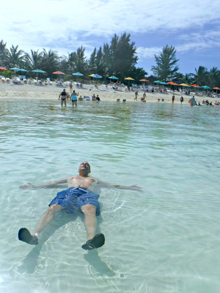 A man lies on his back in the beach of Serenity Bay.