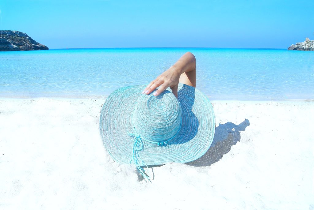 Woman lays on the beach while holding on to her blue beach hat.