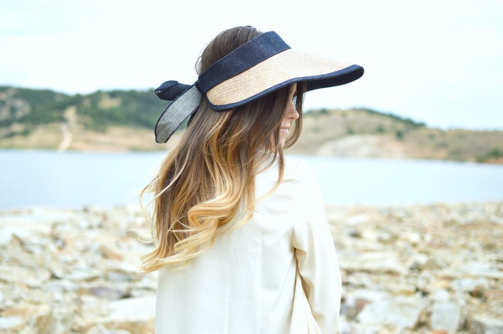 Woman sits by the water and looks to the side, hat hides her face.