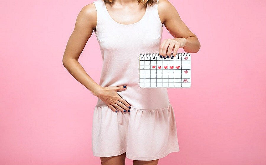 A woman holds her stomach painfully while holding her menstrual cycle marked on a calendar.