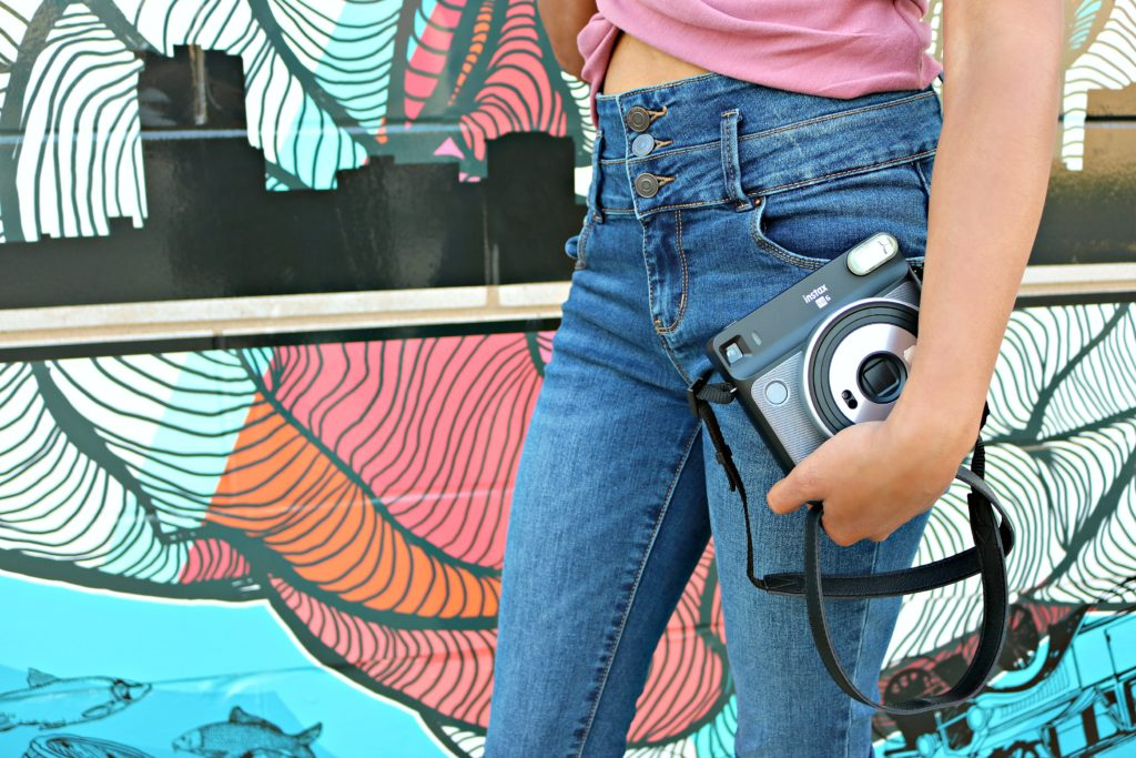 A girl holds a camera in front of a graffiti wall.