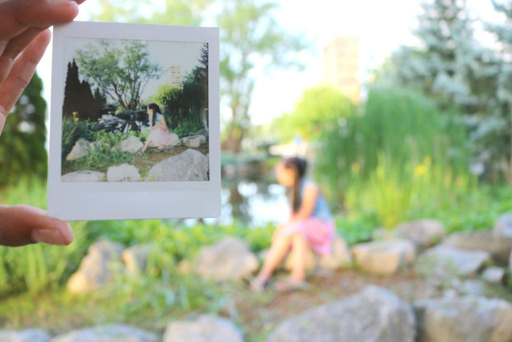 An Instax print is held in front of the camera while the subject is blurred in the background.