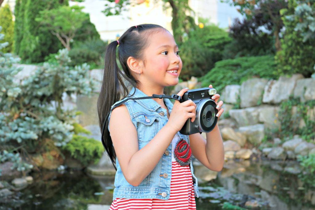 A little girl holds the Instax Square SQ6.