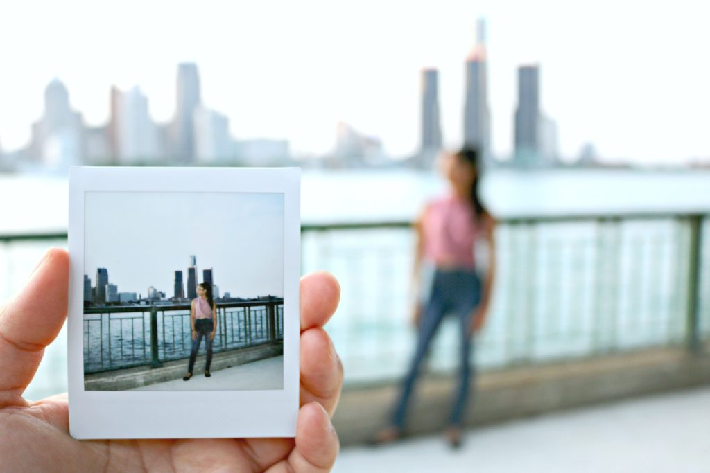 An Instax square print is held up to the camera with a girl and the Detroit skyline in the background.
