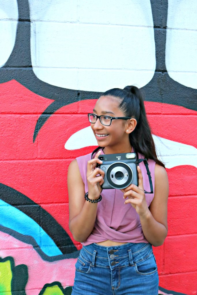 A girl smiles and poses in front of a graffiti wall.