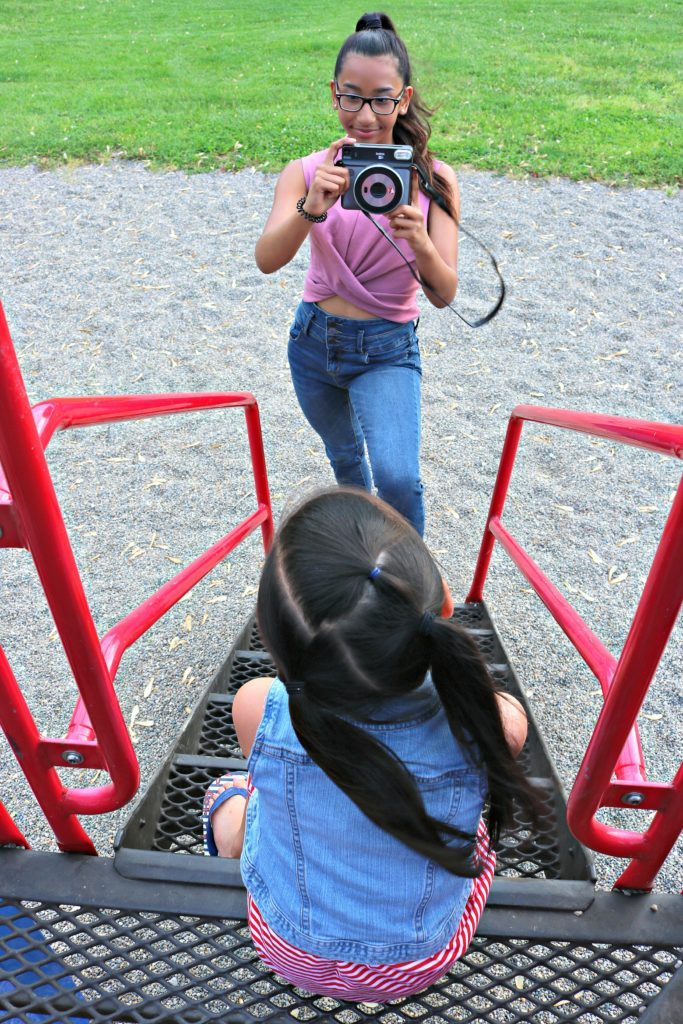 A teen girl takes a picture of her younger sister at the playground.
