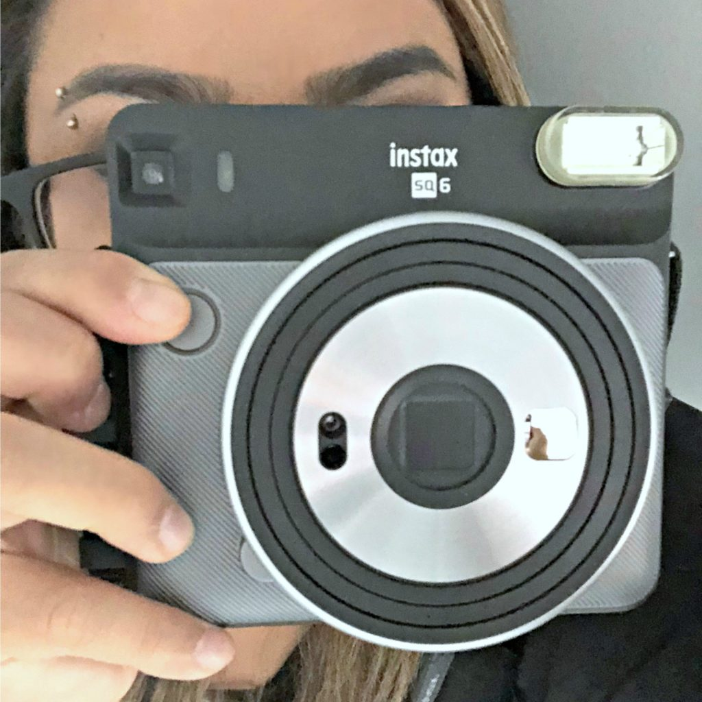 A woman closes in on the camera by pointing an instant camera.
