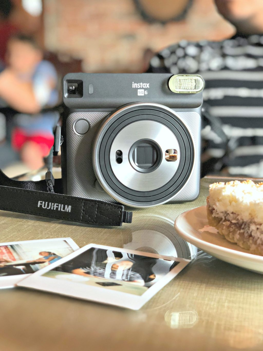 An instax camera with pictures at a cafe.