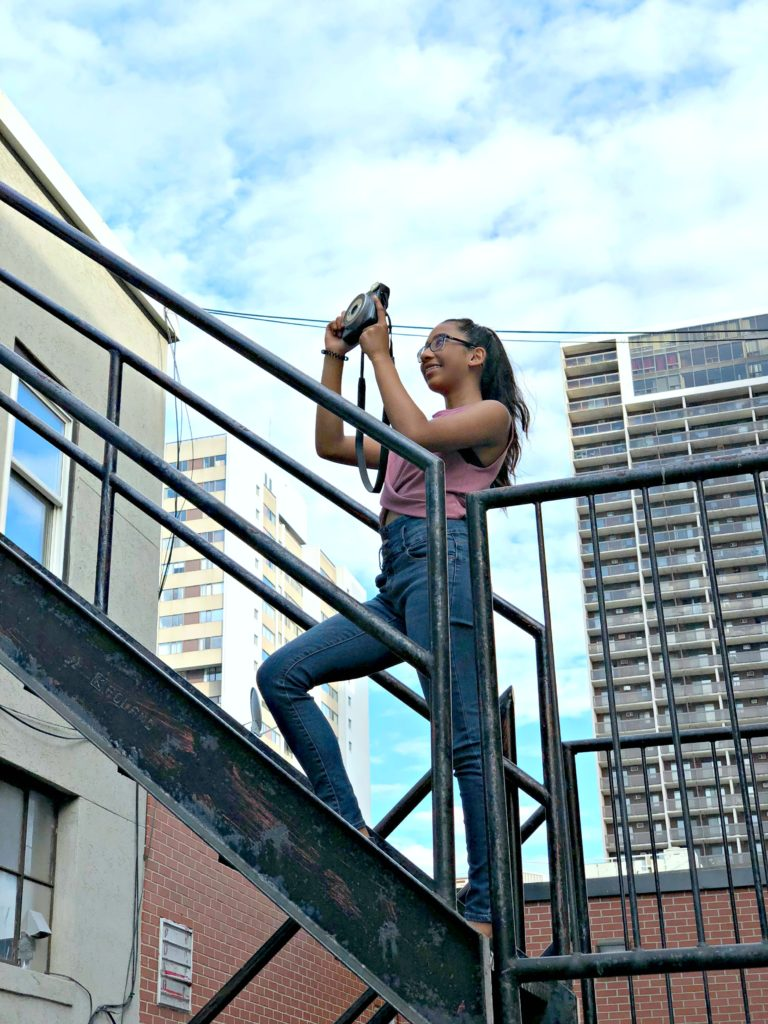 A girl goes up a fire escape to take a snap of a graffiti wall.